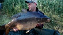 Andrzej Janosz prezentuje złowionego karpia o wadze 16300 kg